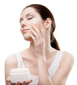 Woman applying emollient cream from container on face — Stock Photo