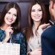 Two girls speak to shop assistant — Stock Photo