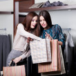 Stock Photo: Two friends buy clothes at cut rates in store