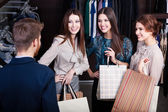 Girls consult with shop assistant — Stock Photo