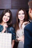 Two girls speak to shop assistant — Foto Stock