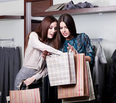 Two friends buy clothes at cut rates in the store — Stock Photo