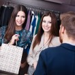 Two girls speak to shop consultant — Stock Photo