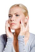 Kobieta bada jej twarz i zmarszczki, które mogą być wyświetlane, na białym tle — Zdjęcie stockowe