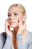 Woman examining her face and wrinkles that can appear, isolated on white — ストック写真