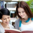 Two smiley students read at the library — Stock Photo