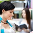 Pretty lady student at the library against bookshelves — Stock Photo