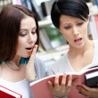 Two wondered students read at the library — Stock Photo #24075357