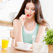 Portrait of the girl eating dieting muesli with milk and strawberry and citrus juice sitting at the kitchen table — Stock Photo #24075621