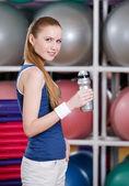 Jovem mulher atlética no sportswear detém uma garrafa de água — Foto Stock