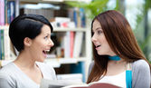 Two glad students read at the library — Stock Photo