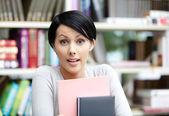 Étudiante avec livre à la bibliothèque — Photo