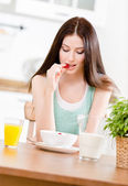 Portrait of the girl eating dieting muesli with milk and strawberry and citrus juice sitting at the kitchen table — Stock Photo
