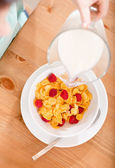 Top view of hand pouring milk into the plate with cereals and strawberry — Stock Photo