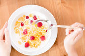 Top view of woman eating muesli with strawberry and milk — Stock Photo