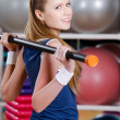 Sportive woman works out with gymnastic stick — Stock Photo