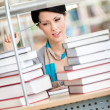 Pensive female student looks at the books — Stock Photo
