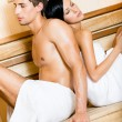 Royalty-Free Stock Photo: Man and lady sitting back to back in sauna