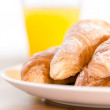 Close up shot of plate with croissants and juice - Stock Photo