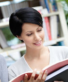 Student looks in book at the library — Stock Photo