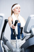 Athletic woman training on simulators in gym — Stock Photo