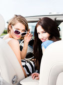 Two girls drive the cabriolet. — Stock Photo