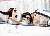 Group of girls with outstretched arms in the car — Stock Photo