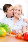 Man kussen mooie vrouw terwijl ze kookt — Stockfoto