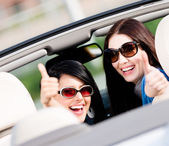 Two girls sitting in the car and thumbing up — Stock Photo
