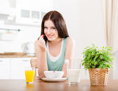 Woman eating strawberry with milk and orange juice — Stock Photo