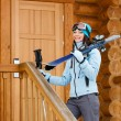 Royalty-Free Stock Photo: Female downhill skier standing near wooden door