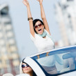 Lovely teenager with her hands up in the car — Stock Photo #26135247