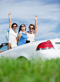 Friends stand in the cabriolet with hands up — Stock Photo
