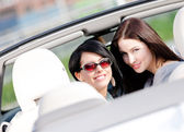 Two happy girls sitting in the cabriolet turn back — Stock Photo