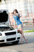 Woman hitchhiking near the broken white car — Stock Photo