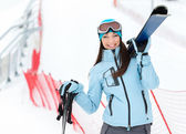 Half-length portrait of female handing skis — Stock Photo