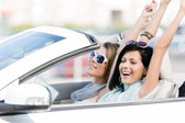 Female friends in the car with hands up — Stock Photo