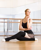 Ballet dancer works out sitting on the floor — Stock Photo