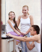 Familj på tre personer borsta sina bucklor — Stockfoto