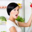 Young woman takes red pepper from opened fridge — Stock Photo #30910951
