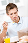 Reading male eats dieting breakfast in kitchen — Stok fotoğraf