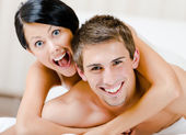 Close up view of laughing couple who plays in bedroom — Stock Photo