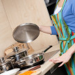 Attractive woman in striped apron cooks in the modern comfortable kitchen — Stock Photo #31271611
