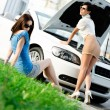 Two girls try to repair the broken car on the road — Stock Photo