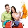 Couple packs suitcase with clothing for trip — Stock Photo