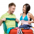 Couple packs suitcase with clothing for traveling — Stock Photo