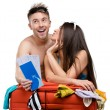 Couple packs suitcase and tries on clothing for traveling — Stock Photo
