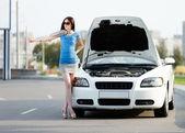 Woman hitchhiking near the broken car — Stock Photo