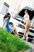 Twee meisjes proberen te herstellen van de gebroken auto op de weg — Stockfoto
