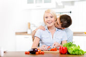 Man kisses woman while she is preparing — Stock Photo